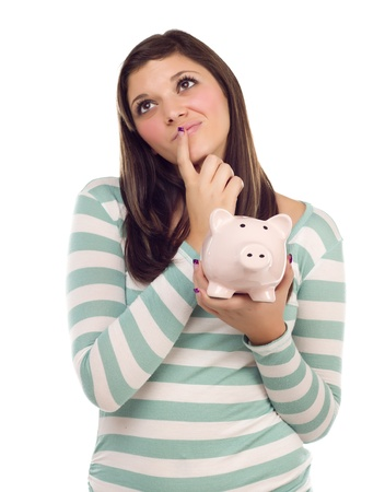 Pretty Ethnic Female Daydreaming and Holding Pink Piggy Bank Isolated on a White Background. photo