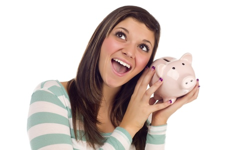 Smiling Pretty Ethnic Female Daydreaming and Holding Pink Piggy Bank to Her Ear Isolated on a White Background. Stock Photo - 10710584