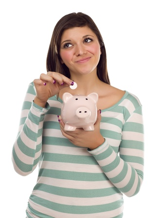 Pretty Smiling Ethnic Female Putting a Coin Into Her Pink Piggy Bank Isolated on a White Background. photo