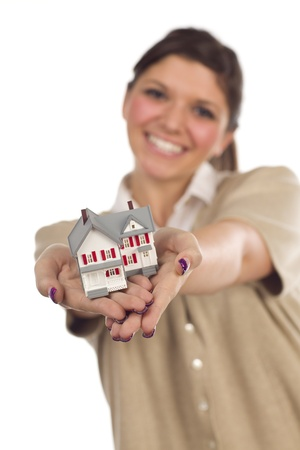Pretty Smiling Ethnic Female Holding Out Small House in Front Isolated on a White Background - Focus is on the House. photo
