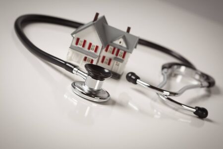 residential market: Stethoscope and Model House on Gradated Background with Selective Focus.
