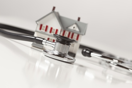 Stethoscope and Model House on Gradated Background with Selective Focus. photo
