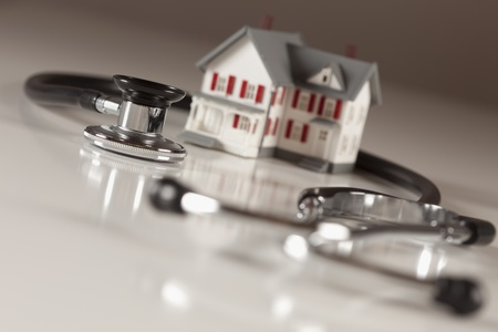 Stethoscope and Model House on Gradated Background with Selective Focus. Imagens - 10826700