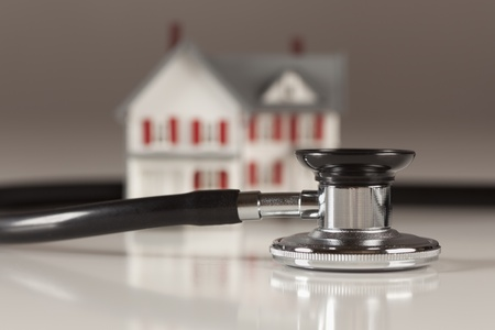housing problems: Stethoscope and Model House on Gradated Background with Selective Focus.