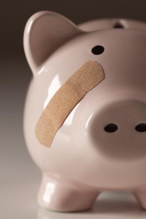 broke: Piggy Bank with Bandage on Face on Gradated Background. Stock Photo