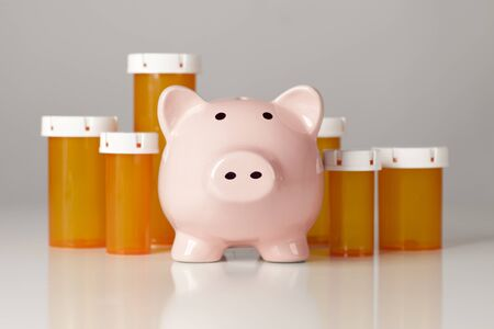 health care fees: Piggy Bank In Front of Several Medicine Bottles on a Gradated Background.