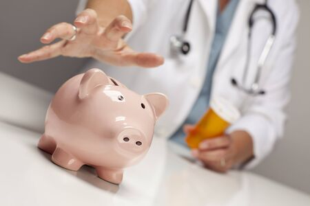hospital fees: Doctor Wearing Stethoscope with Medicine Bottles Reaches for Piggy Bank.