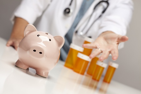 hospital fees: Doctor Wearing Stethoscope Reaches Palm Out Behind Medicine Bottles and Piggy Bank.