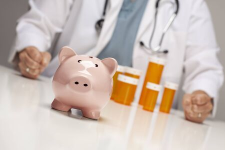 hospital fees: Doctor Wearing Stethoscope with Fists on Table Behind Medicine Bottles and Piggy Bank.