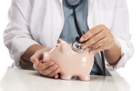 hospital fees: Female Doctor Holding Stethoscope to Pink Piggy Bank Abstract.