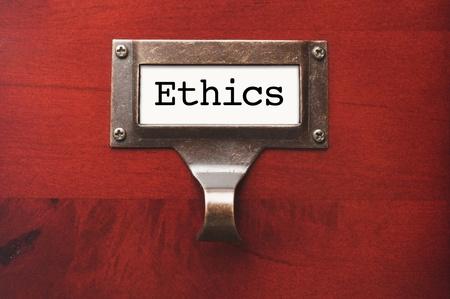etica: Gabinete de madera brillante con la etiqueta del archivo de Ética en luz dramática.