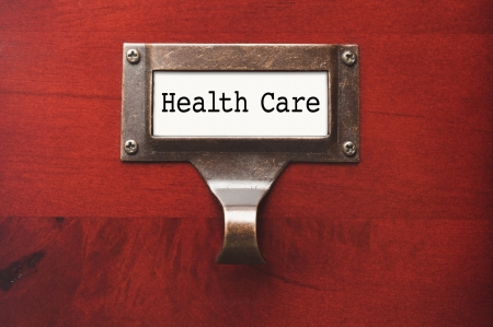 Lustrous Wooden Cabinet with Health Care File Label in Dramatic LIght. photo