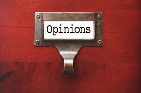 lustrous: Lustrous Wooden Cabinet with Opinions File Label in Dramatic LIght. Stock Photo