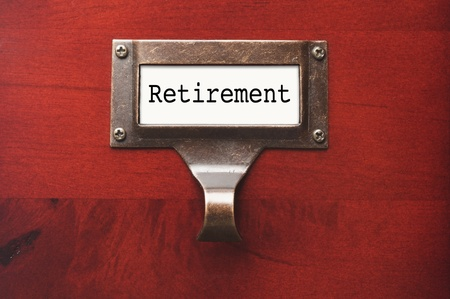 retirement money: Lustrous Wooden Cabinet with Retirement File Label in Dramatic LIght. Stock Photo
