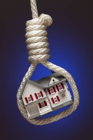 housing crisis: House Tied Up and Hanging in Hangmans Noose on Blue Background. Stock Photo