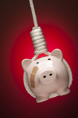Piggy Bank with Bandage Hanging in Hangmans Noose on Red Spot Lit Background.