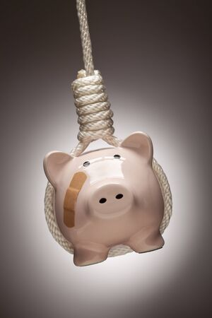 Piggy Bank with Bandage Hanging in Hangmans Noose on Spot Lit Background. photo