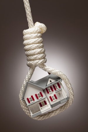 House Tied Up and Hanging in Hangmans Noose on Spot Lit Background. photo