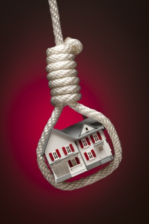 housing crisis: House Tied Up and Hanging in Hangmans Noose on Red Spot Lit Background.