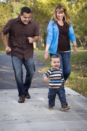 Happy Young Mixed Race Ethnic Family Walking In The Park. photo