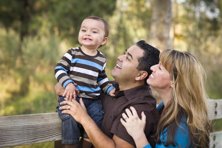 mixed family: Happy Mixed Race Ethnic Family Having Fun Playing In The Park. Stock Photo