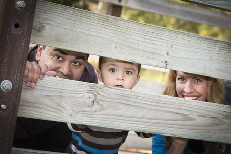 families together: Happy Young Mixed Race Ethnic Family Looking Through a fence In The Park.