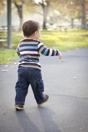 Happy Young Baby Boy Walking in the Park. photo