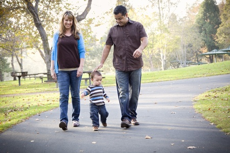 Happy Young Mixed Race Ethnic Family Walking In The Park. Reklamní fotografie