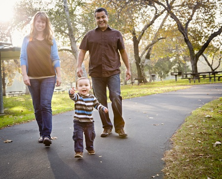 Happy Young Mixed Race Ethnic Family Walking In The Park. Stock Photo