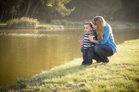 madre soltera: Madre feliz y el Hijo bebé mirando hacia el lago bonito.