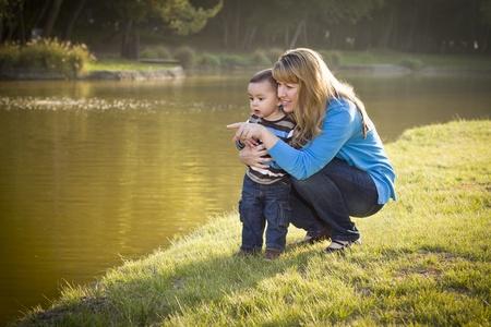 madre soltera: Feliz Madre y el Hijo del bebé que mira hacia fuera en el lago Pretty. Foto de archivo