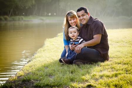 공원에서 초상화를 위해 포즈를 취하는 행복 혼혈 민족 가족.