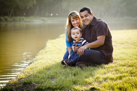 Happy Mixed Race Ethnic Family Posing for A Portrait in the Park. Archivio Fotografico
