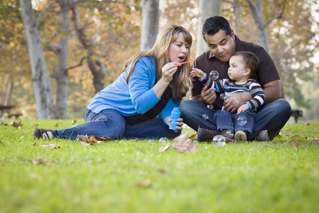 Happy Young Mixed Race Ethnic Family Playing with Bubbles In The Park. photo