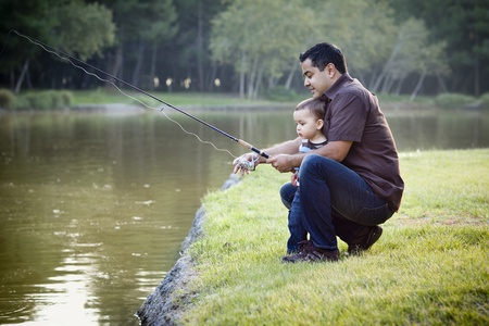 father with children: Happy Young Ethnic Father and Son Fishing at the Lake. Stock Photo
