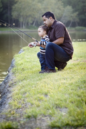 single father: Happy Young Ethnic Father and Son Fishing at the Lake. Stock Photo