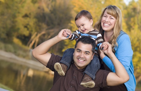 Happy Mixed Race Ethnic Family Posing for A Portrait in the Park. Stock Photo