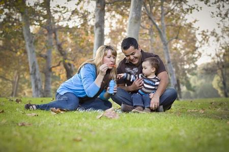 niños latinos: Familia Feliz Joven Raza étnica mixta jugar junto con burbujas en el Parque.