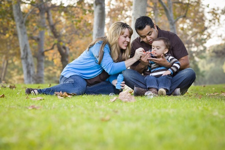 행복 젊은 혼혈 민족 가족 공원에서 거품과 함께 연주.
