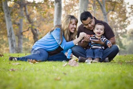 Gelukkig jonge gemengd ras etnische Familie Spelen Samen met Bellen In Het Park. Stockfoto