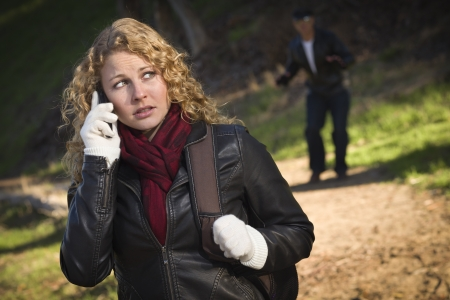 Pretty Young Teen Girl Calling on Cell Phone with Mysterious Strange Man Lurking Behind Her. Stockfoto