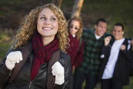 Pretty Young Teen Girl with Three Boys Behind Admiring Her.  photo