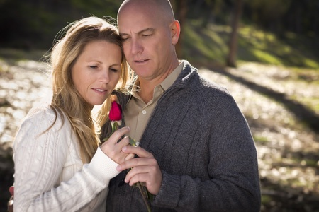 couple having fun: Attractive Young Couple Wearing Sweaters with a Rose in the Park.