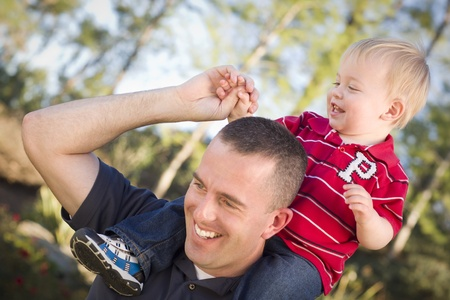 military men: Young Laughing Father and Child  Having Piggy Back Fun. Stock Photo