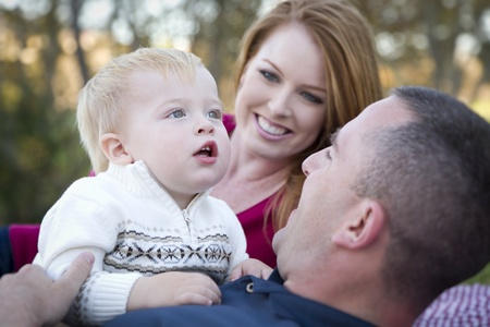 Cute Child Boy Looks Up to the Sky as Young Parents Smile. photo