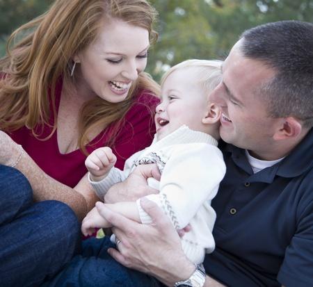 family one: Attraente Giovani Genitori Laughing Boy con il loro bambino nel parco.
