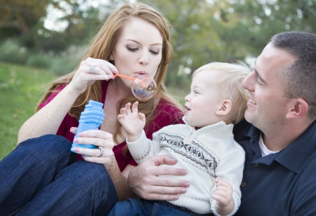 Attractive Young Parents Having Fun Blowing Bubbles with their Child Boy in the Park. Stock Photo - 11396056