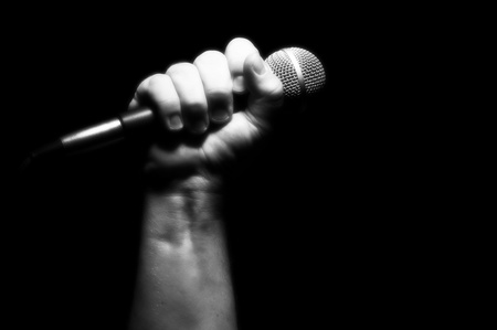 vocalist: Grayscale Microphone Clinched Firmly in Male Fist on a Black Background.