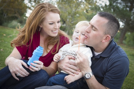 three year old: Attractive Young Parents Having Fun Blowing Bubbles with their Child Boy in the Park. Stock Photo