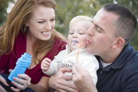 Attractive Young Parents Having Fun Blowing Bubbles with their Child Boy in the Park. photo